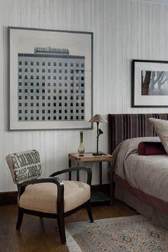 Quarto bonito com papel de parede branco, poltrona baixa, cabeceira estampada e quadro na parede