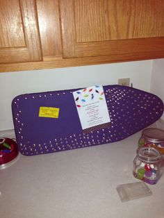 Using an ironing board with push pins as a cork board. Adds unique shape and function