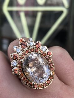 This rutilated quartz ring was designed for a client who loves big and bold jewelry and warm color. We created a halo of burnt orange sapphire surrounding the quartz for extra pop. The entire design is set in 14k yellow gold for an overall warm and glowy effect. A matching tiara band adds even more to this extra bold look. This Rutilated Quartz Ring was commissioned by and named for an Abby Sparks Jewelry client. #uniquejewelry #quartzjewelry #orangeengagementring #boldjewelry #biggemstone