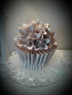 Pearls and pages book bouquet. This book bouquet sculpture tells its story from the inside out by a display of softly folded pages, over one dozen book page origami flowers and elegant pearls . The pearls and pages bouquet was made from a recycled book with the title PS - I Love You. Upon
