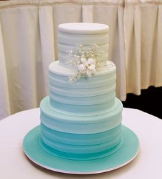 Blue ombre wedding cake with textured layers and a delicate flower spray as an added touch. ᘡղbᘠ