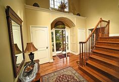 Interior of front entrance with archway over front door, yellow walls, wood floors and high ceiling.