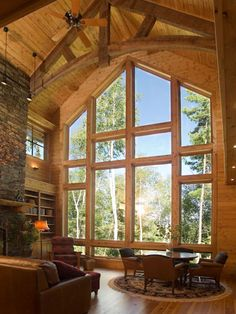 Living Room featuring wall of windows, cathedral ceilings, and fieldstone fireplace in Luxury White Iron Lake Home.  Premier Northeastern Minnesota real estate. Lake homes and cabins in the Ely, Minnesota area.