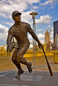 Outside PNC Park, Roberto Clemente statue stands with the Roberto Clemente Bridge in the background Pittsburgh Pirates Baseball, Pittsburgh City, Pittsburgh Sports, Roberto Clemente, Pnc Park, No Crying In Baseball, Baseball Players, Parka, Statue