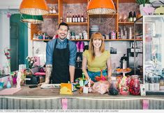 Portrait of male and female baristas standing at cafe counter