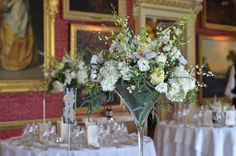 Goodwood House, The Ballroom.  Tables decorated with glass cubes and tall martini vases filled with orchids, hydrangeas, stocks and blossom.  Flowers by Spriggs Florist