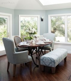 A copper dining table pulls orange from the kitchen's island into the larger open space along with a combination of varying sized and styled seating in a mix of designer fabrics.