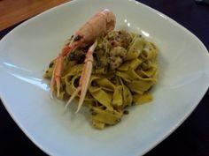 Tagliatelle con Scampi e Pesto di Olive.  Tostare i pinoli, tritarli nel mixer con olive, prezzemolo, sale e olio. Soffriggere l'aglio in una padella con un po' di olio, unire gli scampi privati della testa e del carapace,  cuocere velocemente. Cuocere la pasta, versare il pesto nella padella degli scampi. Spremere nel condimento le teste dei crostacei, allungare con 1 o 2 mestoli di acqua di cottura, cuocere ancora qualche minuto. Scolare le linguine, versarle nella padella e saltare il…