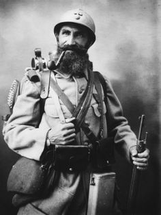"""Le Poilu - the French soldier of WW1: Propaganda photo of what the French """"opinion maker"""" of the day saw as the proverbial Poilu manning France's front line. Not very young, tough, confident, chewing on his pipe, and bearing a variety of kit that was the most modern for the time."""