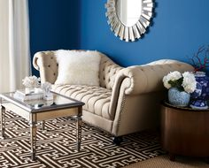 """cream tufted recamier-style sofa with nailhead trim, maze pattern wool rug, mirrored coffee table, Oly antiqued brass bruno cocktail table, """"Blue Suede Shoes"""" wall, sunburst mirror, blue and white porcelains"""