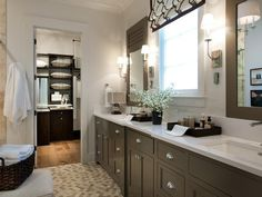 In keeping with the home's twist on traditional design, neutral hues and playful patterns create a relaxing master bathroom escape.  White quartz countertops on his-and-hers vanities complement the gray finish of the cabinetry.  http://hg.tv/vb0t