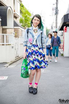 Green-haired Itsuki on the street in Harajuku wearing a Murua denim jacket with a Kikka skirt, cute accessories, and an Evangelion x Clasky bag.