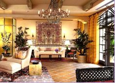 The lobby at Santa Barbara CA Canary Hotel decorated by Michael S Smith:  French styled wing chair, accent pieces for side tables, flat weave area rugs, large hanging Suzani, and the chandelier of my dreams! Take note of the tiled wall behind the sofa!