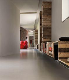 Il corridoio con la libreria di 50 m ispirata alla Linea disegnata da Osvaldo Cavandoli del famoso Carosello. Poltrona rossa Up5 di G. Pesce per B&B Italia. http://www.elledecor.it/case/biella-ex-fabbrica-abitazione-davide-volpe-complesso-industriale#5