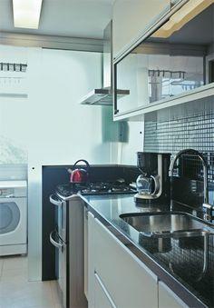 Portas de correr de vidro jateado separam o fogão da área de serviço. Os varais de roupas lavadas não ficam tão visíveis, além de se protegerem parcialmente da gordura e do cheiro de comida. Já a cozinha, sem janelas, ganha luz natural. Pastilhas de vidro causam boa impressão, mas não são lá muito baratas. Usá-las em áreas pequenas – como no frontão da pia – é a dica para gastar pouco, sem abrir mão do charme. O restante dos revestimentos originais foi mantido.