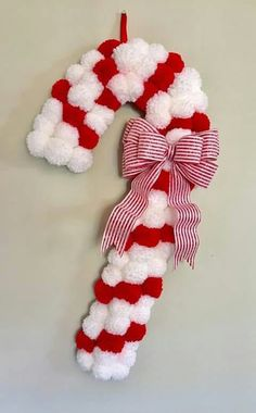 This Candy Cane Pom Pom Wreath adds a modern touch to a classic Christmas decoration. The wreath is made up of over 75 handmade red and white yarn Pom. Christmas Pom Pom Crafts, Crochet Christmas Wreath, Christmas Projects, Holiday Crafts, Christmas Wreaths, Christmas Crafts, Christmas Ornaments, Christmas Candy, Christmas Tables