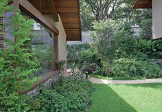 Na lateral oposta, jasmim-da-índia e forração de asistásia. Os pedriscos delimitam o caminho criado na grama esmeralda. No fundo, pitangueira e bela-emília