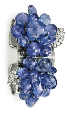 AN ART DECO SAPPHIRE AND DIAMOND CUFF BRACELET, BY CARTIER:  Set at the top with two detachable dress clips, each designed as a cluster of articulated sapphire beads, some trimmed with single-cut diamonds, enhanced by a circular-cut diamond openwork leaf, to the 18k white gold cuff, circa 1935, 2 1/4 ins. diameter, with French assay marks for 18k white gold. Signed Cartier, Paris.  Via Christie's.