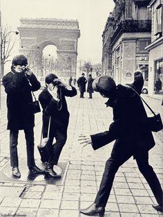George & Paul taking photos of John in Paris, 1964.