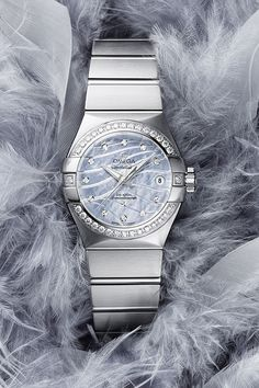 """The #Omega Constellation Pluma has a mother-of-pearl dial, in natural white or blue, which features an engraved, wavy pattern that recalls the shapes of a feather (""""Pluma"""" is Latin for """"feather""""). The blue-dialed version has a case, bezel, and bracelet all in stainless steel. The dials of the Constellation Pluma have 11 diamond indices and a date window at 3 o'clock; the hour, minute and seconds hands are in 18k gold and coated with Super-LumiNova."""