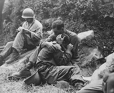 A grief-stricken American infantryman whose buddy has just been killed in action is comforted by another soldier, while in the background a corpsman methodically fills out casualty tags. Haktong-ni area, Korea. August 28, 1950.