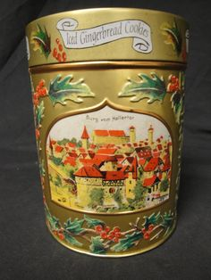 Very Collectible Lambertz Aachen - 1999 - Holiday Musical Iced Gingerbread Cookie Tin. Beautiful Pictures of places in Germany all around the can. Embossed with Holiday branches. Wind up at top of lid. Works great. Looks Great. Marked to bottom: Product of Germany.