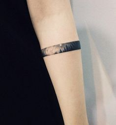 Girls could also go with forest tattoos and here's an enchanting and unique way to get it done. It's a small landscape of a forest at night designed like an armband.