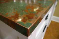 copper patina countertops: mount it on particle board frame with liquid nails, smooth with paint roller, bend genly, staple underneath, spray sealant on top