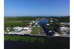 Alina Davis Team - Real Estate Agent in Islamorada, FL  OCEANFRONT WITH DOCKAGE! First time offered for sale in over 20 years! This lot is completely seawalled and has a cut in boatslip. The location is spectacular as the east side is oceanfront and the north side is on the Treasure Harbor channel so there is only one neighbor beside you. Don't miss the opportunity to build your dream home in Islamorada!