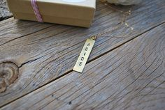 Hand stamped long rectangle charm on a 30inch 14k gold chain.Abide: to remain stable or fixed in a state. To wait for; to endure without yielding; withstand; to bear patiently.