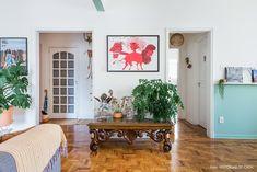 Sala de apartamento alugado com paredes pintadas, plantas e móveis reutilizados