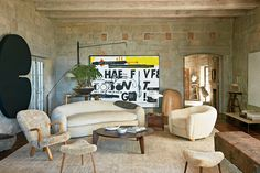 . Seen here in Ellen DeGeneres Tuscan-style villa in Santa Barbara is Royère's Ours Polaire (or Polar Bear) sofa and matching chair, as well as a Jean Prouvé coffee table, a sheepskin chair by Philip Arctander and Danish stools from the 1960s.