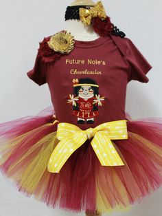 Your little Nole girl will look so adorable in this Cheerleader outfit. The outfit includes an appliqued cheerleader bodysuit, a crimson and gold ribbon tie tutu, and a matching headband in FSU colors. This little outfit is perfect for your future Nole cheerleader to wear for tailgating or any Nole game day get together. The bodysuit can be personalized for FREE. I never charge for personalization on outfits. Just put your child's name in the notes section of your order. This can be made for…