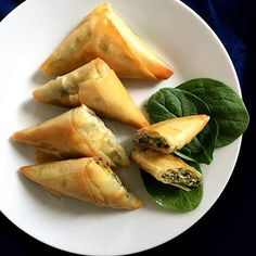 Greek Spanakopita triangles with spinach and cheese, a delicious snack or starter that will impress everyone having a bite.