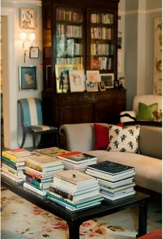 Books everywhere! Beautiful bookcase and books piled on a coffee table.love this room.