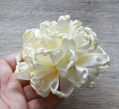Ribbon flowers ~Small lengths of satin ribbon are knotted in middle of each piece of ribbon, then knotted lengths are gathered together to form flower. it is very simple.
