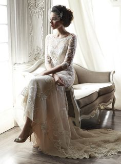 Maggie Sottero Wedding Dresses, Spring 2015. The color is ivory over nude.A dramatic illusion lace back and illusion sleeves adorn this hand-embellished sheath gown, glimmering with metallic lace appl
