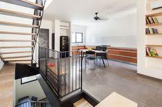 קירות המטבח כוסו באריחים לבנים ופשוטים, משטח העבודה עשוי פלטות בטון מיובאות, שהותקנו בידי בעלי הבית. המדפים בסלון נחתכו מאותו עץ סנדוויץ' פשוט, שממנו עשויות המדרגות ( צילום: טל ניסים )
