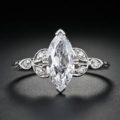 A super high-quality 1.18 carat antique marquise-cut diamond is the star of this stunning vintage platinum diamond engagement ring. The diamond is accompanied by a GIA report stating D color, VS2 clarity. Three small accent diamonds are set on either side and further enhanced with a decorative design down each shoulder. Platinum. Art Deco. Interesting use of the marquise