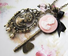 Beautiful vintage style charm necklace, made of a large key with a soft pink victorian resin cameo, a pink crystal, an antique bronze large cameo