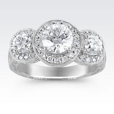 This vintage-inspired halo design combines one center round diamond at approximately 1.01 carats TW, and 40 other hand-matched round diamonds at approximately .91 carat TW, to truly catch everyone's attention. Set in beautiful 14 karat white gold with gorgeous hand-engraving, the total diamond weight is approximately 1.92 carats.