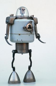 "Stlko is named for his finned aluminum torso - an old add-on car filter which was designed to utilize a roll of bum paper as the disposable filter...21"" tall. The body is a vintage child's tin washing machine."
