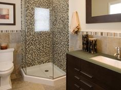 A brown and beige mosaic tile shower with a glass enclosure is a focal point in this serene bathroom. A sleek wood vanity and matching mirror provides sharp, clean lines for a tidy look.