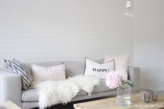 Grey couch put white pillow in front of green accent pillows or get vintage center cream pillow (e.g feed bag pillow) and fold blanket over corner