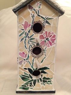 This pretty little birdhouse is perfect for the bird divas in your yard or as an eclectic accessory for your home! It's made of wood and has been