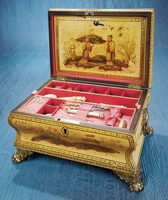 Early 1800s English Workbox. Has original painted Chinoiserie finish with richly designed Chinese scenes and symbols in shades of gold,red,green and brown. interior pink lining,a back flap designed to hold papers. Compartmented base that contains various sewing tools including glass pearl pins in pincushion and a set of gold tools in fitted recesses including scissors,thimble,needle case and stiletto. tool tray lifts out for access to hidden compartment