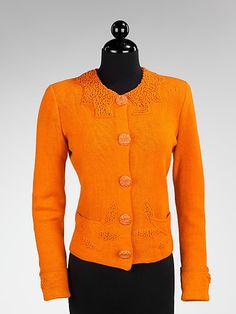 This eye-catching orange sweater, from a 1938-1940 collection 1938 shows Schiaparelli was continuing to provide knitwear for her clients. This particular example employs both trompe loeil elements and unusual buttons, both components featured in countless Schiaparelli designs. The twisted knit looks like Persian lamb fur, a play on texture, and creates trompe loeil fur cuffs and collar. The buttons were probably executed by Jean Clement or Roger Jean-Pierre.