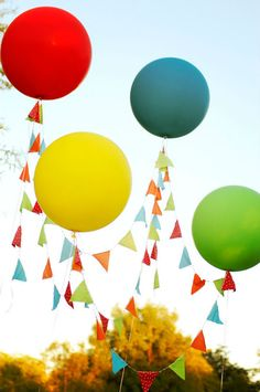 love the use of these over-sized balloons to hold up colorful bunting as a focal point; TIKKIDO found via The Party Wagon
