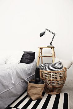 Lots of lovely things: big wicker basket of cushions; step ladder as side table; anglepoise lamp.