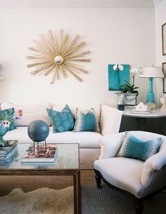 White walls and furniture with turquoise accent accessories.